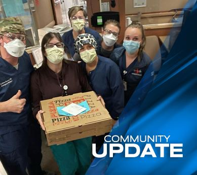 Photo of Mercy Hospital staff members holding pizza